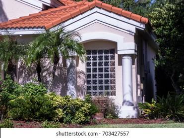 glass block window shadowed by palm trees
