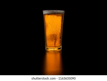 glass of blond beer on black background