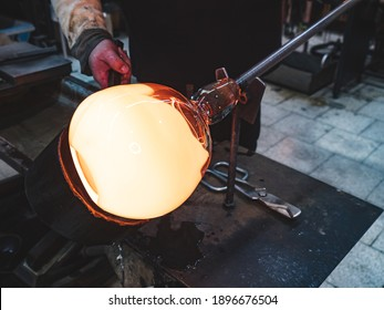 Glass blower forming hot piece of glass with wooden tool. Traditional glass crafter works with  burning and blowing an art piece. Hand made glass studio in Kunratice.