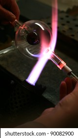 Glass blower forming a piece of decorative glass.