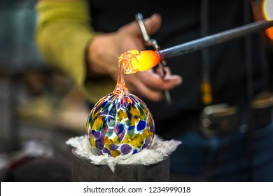 A Glass Blower Shaping Molten Glass into a Piece of Art
