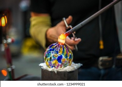 A Glass Blower Shaping Molten Glass into a Piece of Art