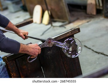 Glass blower at work shaping molten glass, murano venice