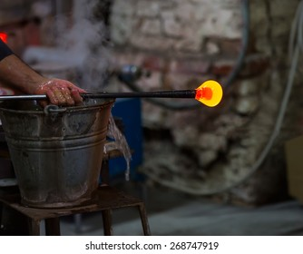 Glass blower at work shaping molten glass, Murano, Venice, Italy