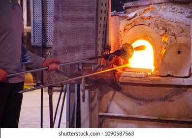 Glass blower working molten glass in an oven in a factory in Murano Venice, Italy