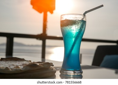 A glass of blue cocktail with pizza on the roof top bar on seascape background. Selectived focus. Colorful cocktail to celebrate on happy relaxing cheerful day. Soft drink on sunset beach.