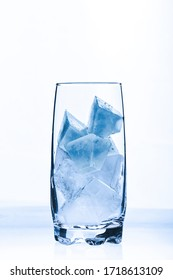 A glass with blue ice cubes against a white background
