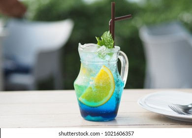 A glass of blue italian soda drink on the table. Fresh drink with yellow lemon in colorful soda. Summer drink with pepper mint leaf in sunny day