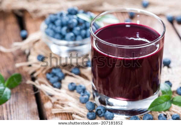 Glass with Blueberry Juice and fresh fruits (close-up shot)