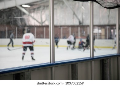 Glass boards at an ice hockey rink with blurry players behind