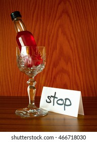 Glass, bottle with alcohol and paper with text STOP. Appeal to overcome addictive alcohol abuse and dependence through detoxifiction, treatment, rehabilitation and abstinence