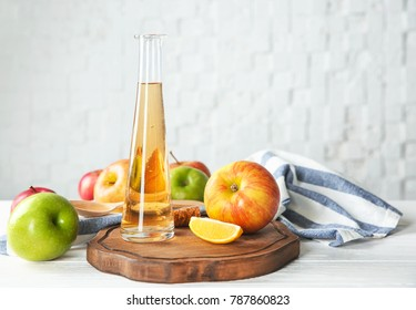 Glass bottle with apple vinegar and fresh fruit on table