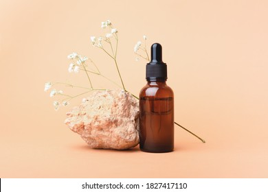 A glass bottle with aromatic oil or serum on a stone and little twig with flowers near. Natural Organic Spa Cosmetic concept. Front view.