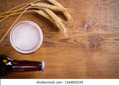 Glass and bottle of beer, ears of barley on wooden background. Ale. overhead, horizontal with copy space