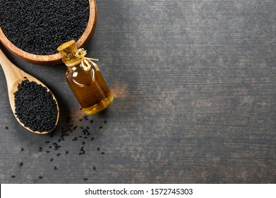 glass bottle of black cumin seeds essential oil , Nigella Sativa in spoon and bowl on wooden rustic background. Organic herbal medicine for many diseases, black cumin