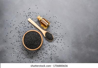 glass bottle of black cumin seeds essential oil , Nigella Sativa in spoon on rustic table. Organic herbal medicine for many diseases, black cumin