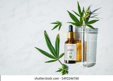 Glasflasche mit Cannabisöl mit Etikett und einem Reagenzglas mit Hanfblättern auf Marmorhintergrund. Kopiert Platz.