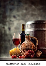Glass, bottle, carafe of wine and barrel shot with selective focus