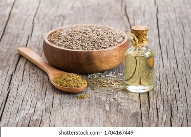 Glass bottle of Caraway seeds essential oil with caraway powder in wooden spoon on rustic table ( Cuminum cyminum )