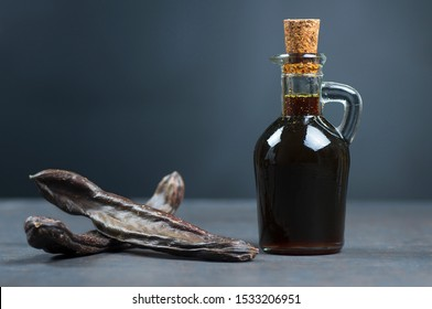 glass bottle of carob molasses and carob pods on rustic background, locust bean healthy food, Ceratonia siliqua ( harnup )