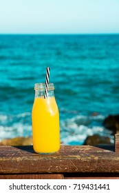 Glass bottle with citrus fruit juice orange with straw on wooden rail. Turquoise sea and blue sky in the background. Tropical vacation summer clean eating concept