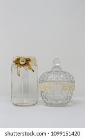 A glass bottle, container and lid, decorated with handmade ribbons and ornaments like a button and a white wooden heart.