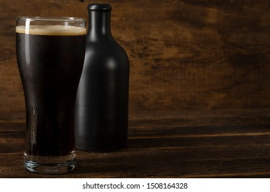 glass and bottle of dark beer on wooden table with shadow