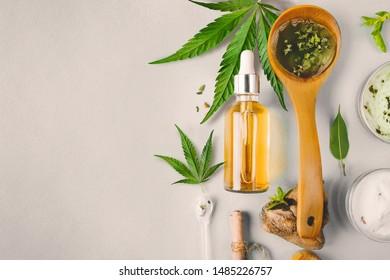 Glasflasche und Tröpfchen CBD ÖL, THC Tinktur und Cannabisblatt auf Hintergrund. Laborproduktion von Kosmetika mit CBD-Öl.