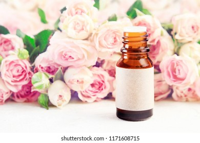 Glass bottle of essential oil with empty craft label on table with roses pink soft blurred background. Aromatherapy spa product