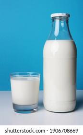 Bouteille de verre de lait frais avec son verre complet pour un bon petit déjeuner. Photo isolée sur fond bleu avec ombre