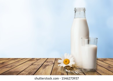 Glass and bottle with fresh milk on table against color background. Space for text          - Image