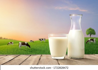 Glass and bottle of fresh milk on wooden table with cows on green meadow and mornig light background.