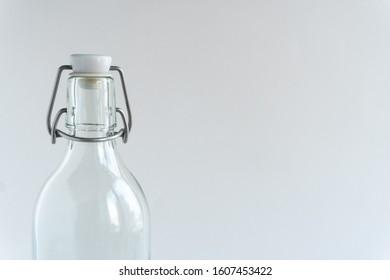 Glass bottle at gray monochrome background. Zero waste concept. Minimalist lifestyle. Copy space.