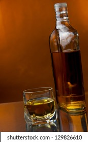 a glass and a bottle of hard liquor at warm backdrop