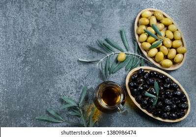 Glass bottle of homemade olive oil and olive tree branch, raw turkish green and black olive seeds and leaves on grey rustic table. olives background, olivae oleum