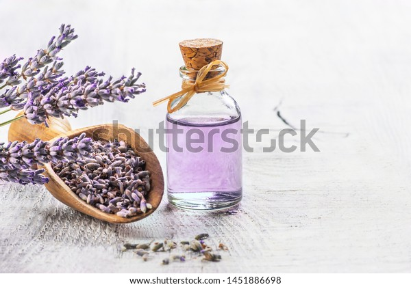Glass bottle of Lavender essential oil with fresh lavender flowers and dried lavender seeds on white wooden rustic table, aromatherapy spa massage concept. Lavendula oleum