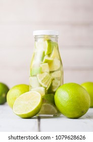 Glass bottle of lime slices still fruit water and raw limes on white wooden background