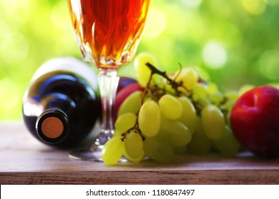 glass and bottle of madeira wine, fruits on table