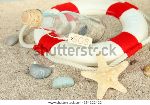 Glass of bottle with note inside on  sand background