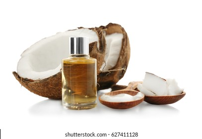 Glass bottle with oil near fresh coconut on white background