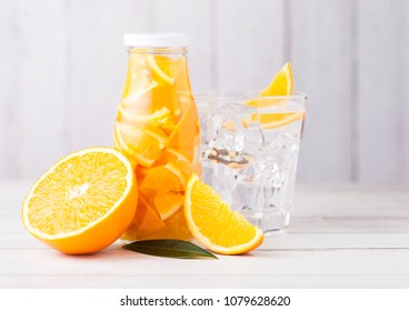Glass bottle of orange still fruit water and glass with ice cubes and raw oranges on white wooden background