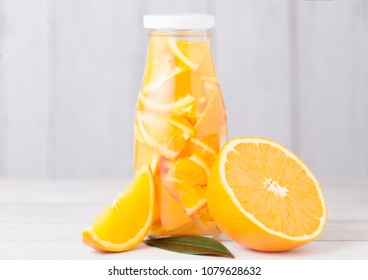 Glass bottle of orange still fruit water and raw oranges on white wooden background