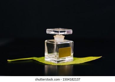 Glass bottle with perfume on a black background. Green leaf. Aromas of freshness