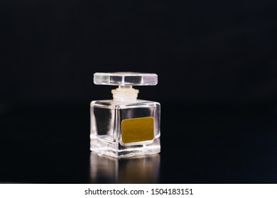 Glass bottle with perfume on a black background.