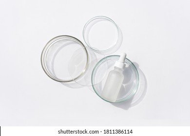 Glass bottle in petri dish on white background. Top view, flat lay. Concept skincare. Dermatology science cosmetic laboratory. Natural medicine, cosmetic research, organic skin care products.