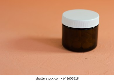 Glass bottle for pills. Beautiful peach background.