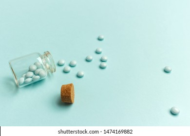 Glass bottle with pills scattered on a turquoise background. Drug poisoning, suicide attempt concept.