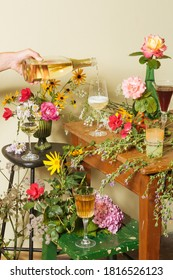 A glass and a bottle of prosecco among many colorful flowers, to suggest the complexity of the wine's scents