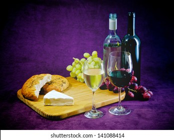 A glass and bottle of red and white wine, with bread grapes and cheese, plenty of room for text
