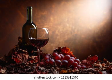 Glass and bottle of red wine on a table with grapes and dried up vine leaves. Copy space.